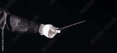 Photo hand in a white glove with a magic wand on a black background