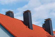Chimney On Blue House With Red Roof  In Europe