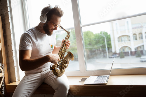 Cuadros en Lienzo Caucasian musician playing saxophone during online concert at home isolated and quarantined