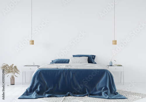 Fotografía Bedroom interior with a blue bedspread against a white wall background