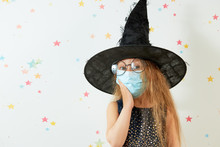 Happy Halloween On Quarantine Coronavirus Pandemic. Little Girl Child In Witch Carnival Costume And Face Protection Mask.