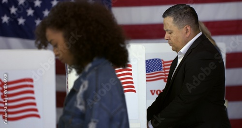 Valokuva MS Hispanic man at polling station, votes in a booth with young Hispanic woman i