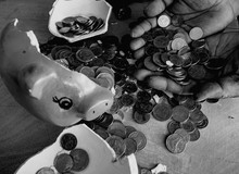 Cropped Hand Holding Coins By Broken Piggy Bank At Table