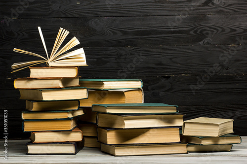 Open book, hardback books on wooden table Fototapeta