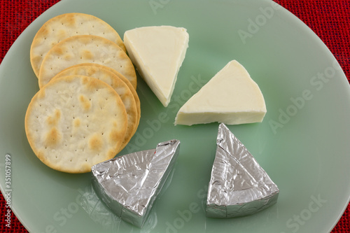 Brie cheese mini slices unwrapped and wrapped in aluminum foil packages and tabl Canvas-taulu