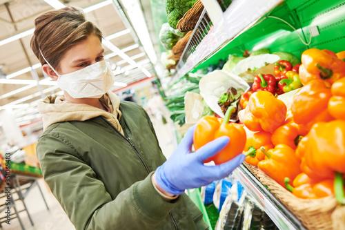Fototapeta man in mask and protective gloves buying food in shop at coronavirus epidemic obraz