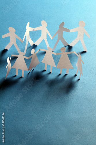 Close-up Of Paper Figures Holding Hands