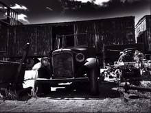 Abandoned Vintage Car Against Cargo Container In Junkyard
