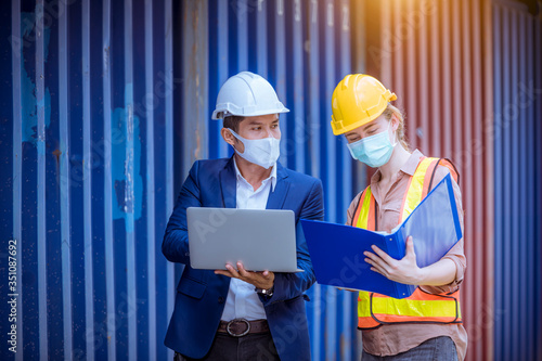 A Manager and dock worker under discussion about dock container shipping warehouse document, they wearing safety uniform hard hat ,face mask and hold radio communication Tapéta, Fotótapéta