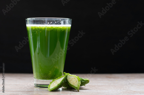 Photo Herbal juice with bitter melon or bitter gourd on black background