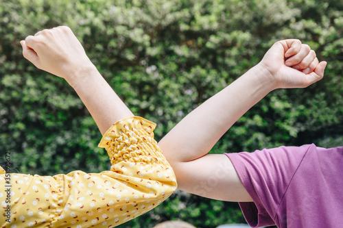 Photo Cropped shot of two woman bump elbows for greeting during coronavirus epidemic