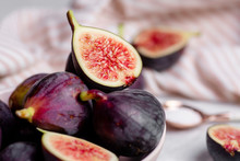 Close Up Of Halved And Whole Purple Figs In A Bowl With A Pink And White Striped Napkin And Rose Gold Spoon Full Of Sugar In The Blurred Background