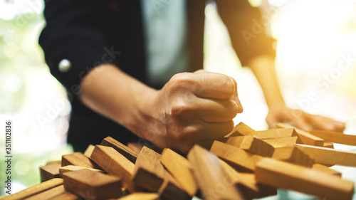 Fototapeta Businesswoman get angry and smashed down wooden blocks of Tumble tower game on table obraz