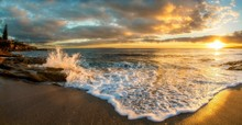 Waves Splashing On Beach Against Cloudy Sky At Sunset