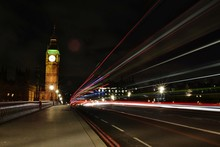 Light Trails Over Street Against Big Ben At Night In City