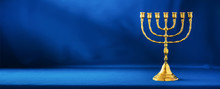 Golden Hanukkah Menorah On Blue Background. Jewish Holiday Banner With Copy Space. Ancient Ritual Religious Candle Menorah