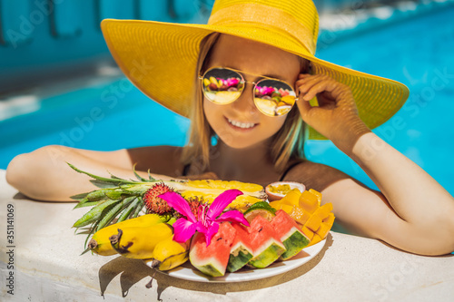 Fototapeta Young woman relaxing and eating fruit plate by the hotel pool. Exotic summer diet. Photo of legs with healthy food by the poolside, top view from above. Tropical beach lifestyle obraz