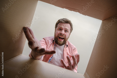 Fotografija Upset man found the wrong order in the unpacked delivered box and inquiringly makes a gesture with hands