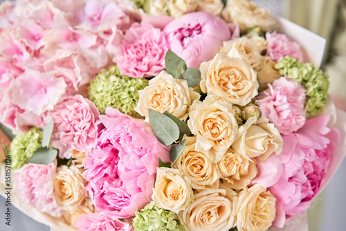 closeup Pink peonies and hydrangea. Beautiful bouquet of mixed flowers in woman hand. Floral shop concept . Handsome fresh bouquet. Flowers delivery. © malkovkosta