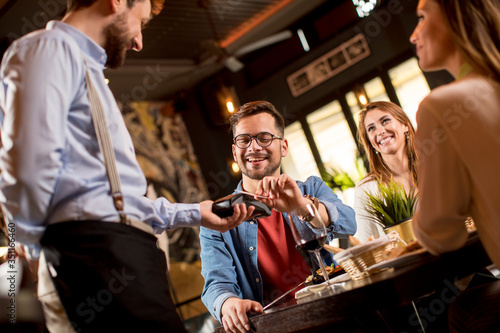Young man paying with contactless credit card in restaurant after dinner Tapéta, Fotótapéta