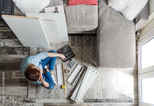 Fototapeta Young woman assembling new furniture for home. House assembling furniture concept. obraz