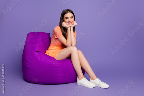 Full body profile photo of funny cheerful lady sit cosy bean bag dreamy good mood chin on arms wear casual orange striped t-shirt jeans mini skirt isolated pastel purple color background