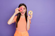 Leinwanddruck Bild - Photo of pretty funky lady long straight hairstyle hold hand fresh glazed doughnuts looking like specs wear casual orange striped t-shirt isolated pastel purple color background