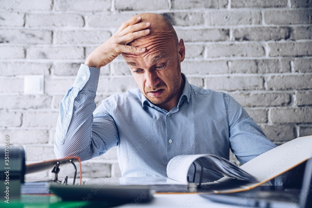 Fototapeta Finacial problems and crisis. Stressed depressed man reading bills and loan contract. Finacial problems and crisis
