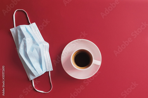 Fototapeta top view of a coffee cup and removed medical surgical mask on a red table. Concept of protection. Minimal concept of health and allergies.  space for a text.  obraz na płótnie