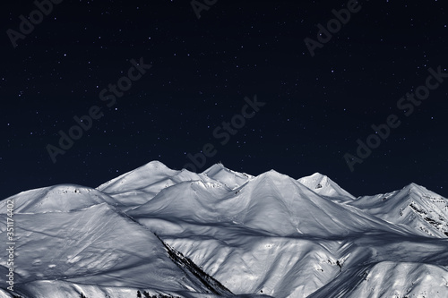 Snowy high mountains and dark starry sky at winter night Wallpaper Mural