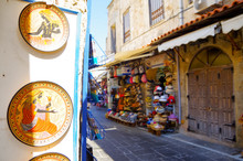Picturesque Scenic Narrow Alleys With Traditional Cobblestone Streets And Souvenir Shops In Old Town Of Rhodes City In Famous Tourist Attraction Rhodes Island In Dodekanes Greece During Summer Cruise