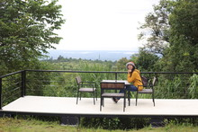 A Woman Sitting In A Chair At The Mor Hin Khao National Park In Chaiyaphum, Thailand