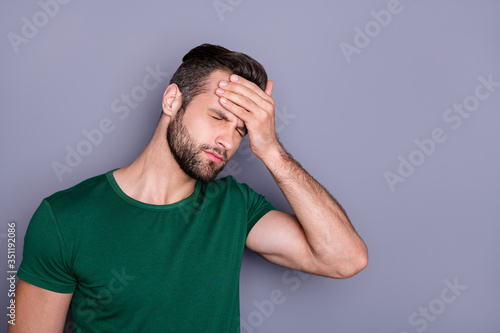 Obraz Photo of attractive handsome guy hold hand on forehead fever eyes closed grimacing caught cold corona virus temperature wear casual green t-shirt isolated grey color background - fototapety do salonu
