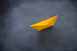 image of single paper boat over blackboard background
