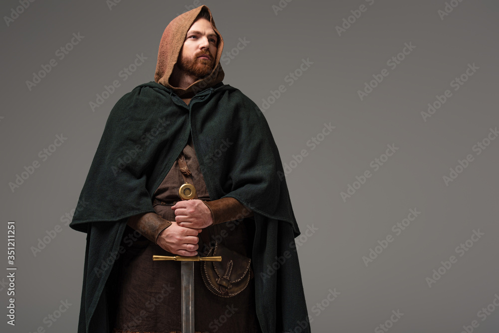 Fototapeta medieval Scottish redhead knight in mantel with sword on grey background