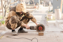 Worker Cuts Paving Slabs With Circular Cutter In Open Air.