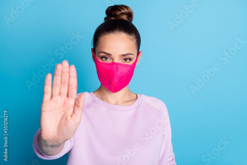 Fototapeta Stay away. Closeup photo of pretty lady keep social distance raise palm arm don't let people contacting her wear protect bright face mask sweater isolated blue color background obraz