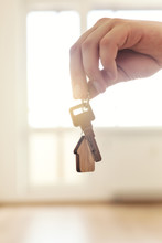 Home Key In Hand In Apartment On Empty Room Background