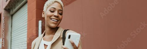 Fototapeta Happy black businesswoman using her smartphone obraz