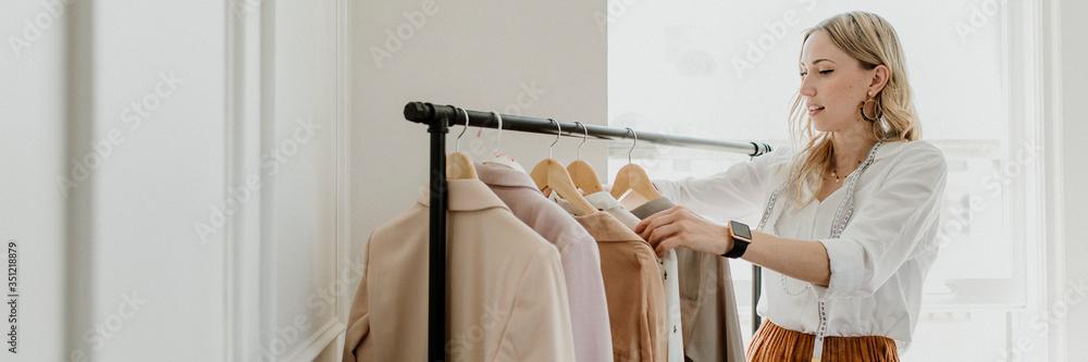 Fototapeta Fashion stylist sorting the clothing rack