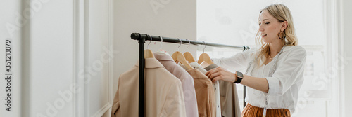 Fototapeta Fashion stylist sorting the clothing rack obraz