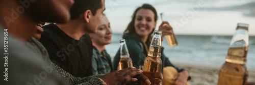 Obraz na plátne Cheerful friends drinking by the seaside