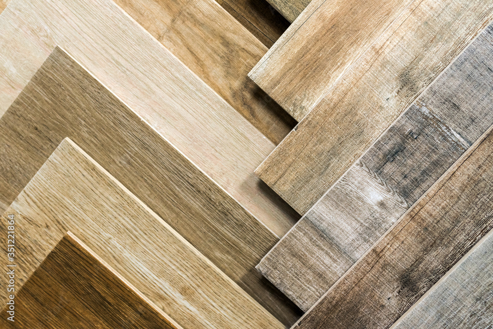 Fototapeta Variety of wooden like tiles. Samples of fake wood tiles for flooring. Assortment of floor laminate / tiles in an interior shop.