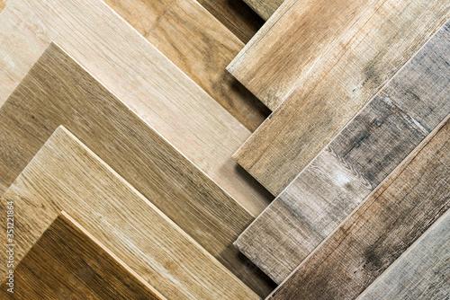 Obraz Variety of wooden like tiles. Samples of fake wood tiles for flooring. Assortment of floor laminate / tiles in an interior shop. - fototapety do salonu