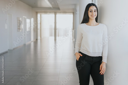Fototapeta Smiling young woman going to a job interview in a corporation obraz
