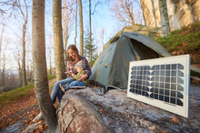 Focus On Small Solar Panel In A Campsite On A Sunny Autumn Day Against The Background Of A Young Family. Mom And Child Watching Something At A Mobile Phone While Enjoying Outdoor Activities