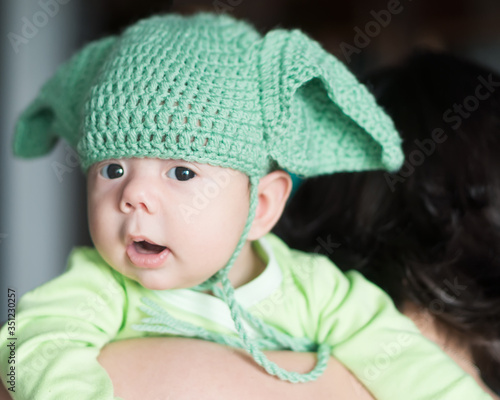Newborn baby in the crotchet green cap with ears looks like one famous  star master character Wallpaper Mural
