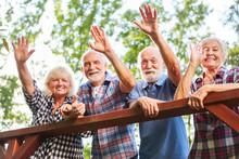 Happy Seniors Wave From A Bridge