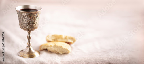Unleavened bread, chalice of wine, silver kiddush wine cup on canva background Fototapet