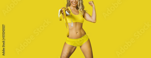 Fotomural Happy woman with tape measure in her hand - successfully losing weight concept